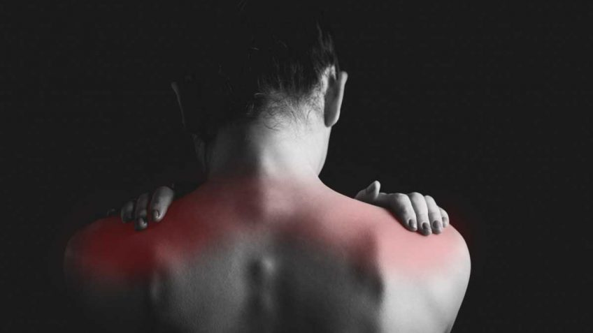 Back of woman rubbing her shoulders with red showing muscle pain